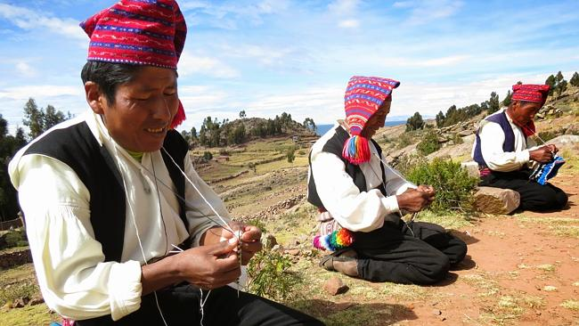 A group of Taquile men share each others company while working on their knitting.