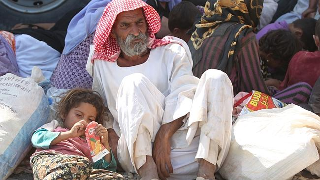 Displaced Yazidis rest at the Syrian-Iraqi border yesterday after fleeing the slaughter.