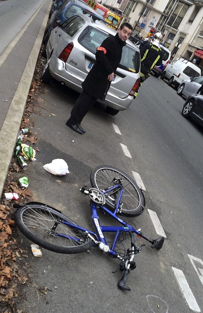 A police officer stands next to the bicycle of a police officer who was hit by a car near