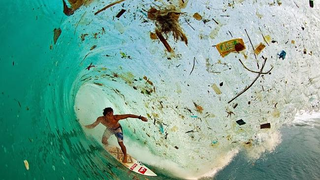 Trash Wave: Indonesian surfer Dede Surinaya catches a wave in a remote but garbage-covere