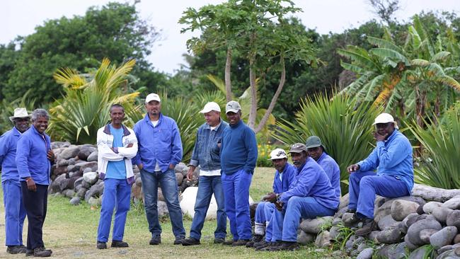 Saint-Andre city workers ... take a break from cleaning the beach to watch multi national