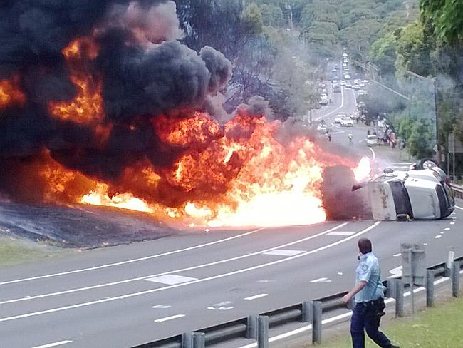 A police officer runs for safety as the tanker burns. Picture: Stuart de Low
