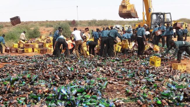 Beer we go ... Police set about destroying the bottles. Pic: Aminu Abubakar.