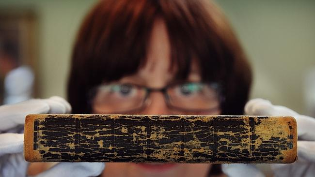 Helen Mitchell holding the 1669 Bible which was found among a stack of random books.