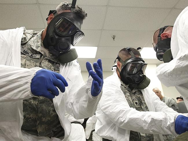 Soldiers don gas masks while training on how to put on protective clothing and gloves as