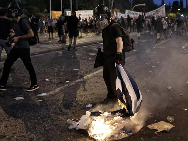 A protester burns a Greek flag.