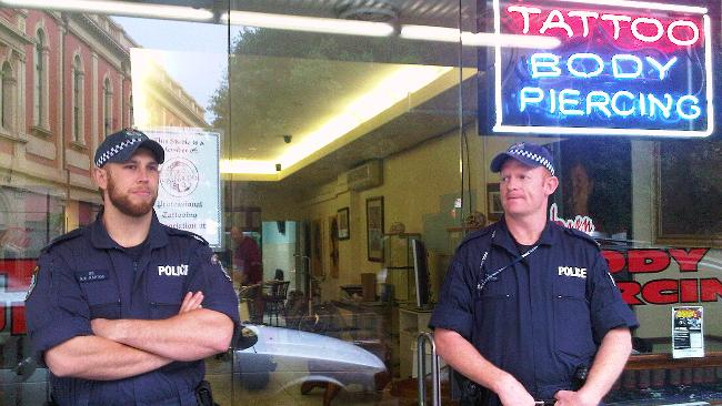 Police officers stand guard outside Scott Orrock's tattoo palour in Newtown.