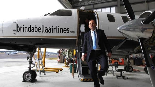 Tony Abbott disembarks from a Brindabella Airlines plane in Canberra during his time as opposition leader.