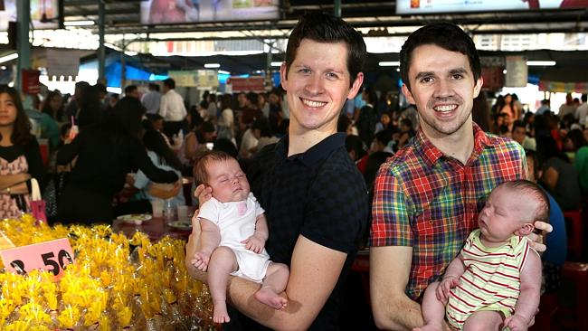 Matt, left, holds Estelle while Mark holds Tate in a busy Bangkok food market. Picture: Dean Martin.