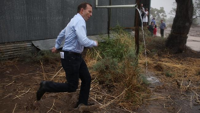 Tony Abbott dashes through a downpour after meeting graziers in drought-hit Bourke in NSW. Picture:  Andrew Meares