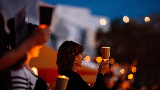 People hold candles at Light the Dark - a vigil in response to tragic turn of events on M