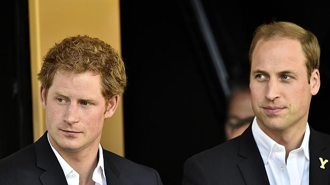 Britain's Prince William, Duke of Cambridge (R) and his brother Prince Harry stand on the
