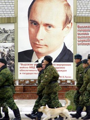 Military Icon ... Russian soldiers march next to a giant poster of the Russian President