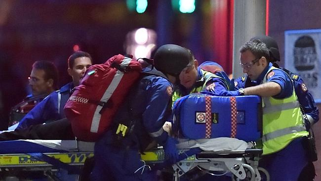 Australian paramedics treat an injured hostage as other hostages are carried out of a caf