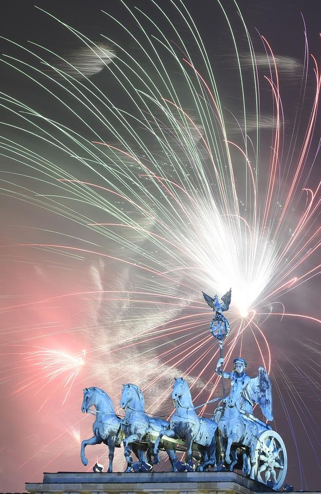 Fireworks explode ... behind Berlin's landmark Brandenburg Gate to usher in the new year.