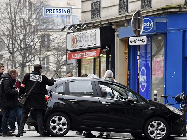 Investigation ... French police and forensic experts examine the car used by armed gunmen