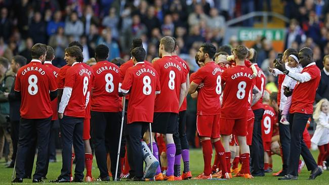 Liverpool players wear T-shirts bearing the name and number of Steven Gerrard after the m