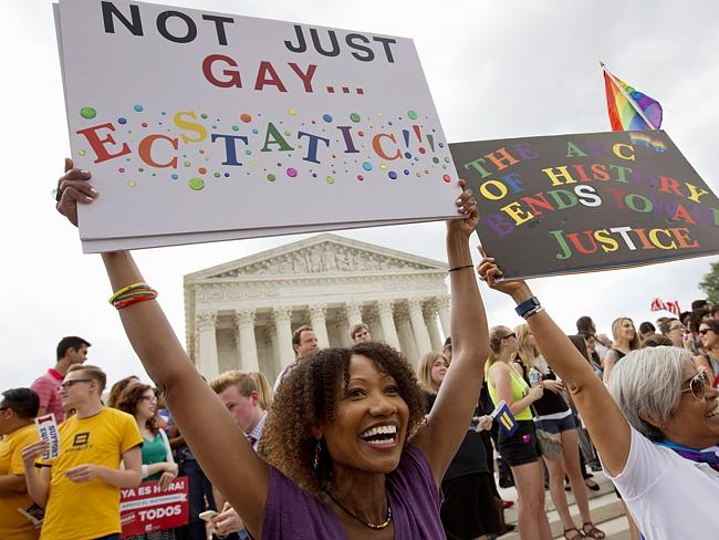 Gay and happy ... Ikeita Cantu, left, and her wife Carmen Guzman, hold up signs as they c