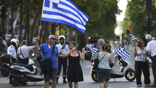 Global push ... Protesters in Paris hold Greek flags as they rally in support of the peop