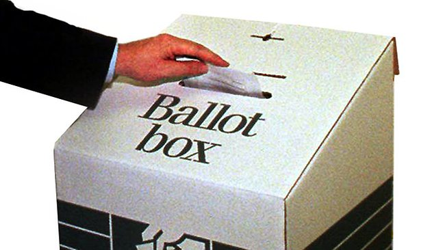 voter placing his vote in ballot box