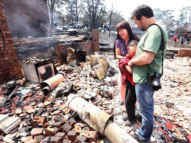 Evangeline Love returns to her house destroyed by bushfire in Winmalee with her son Jomei and brother-in-law Ruben Love.