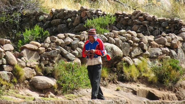 A young Taquile Island resident knits a beanie as he walks between settlements.