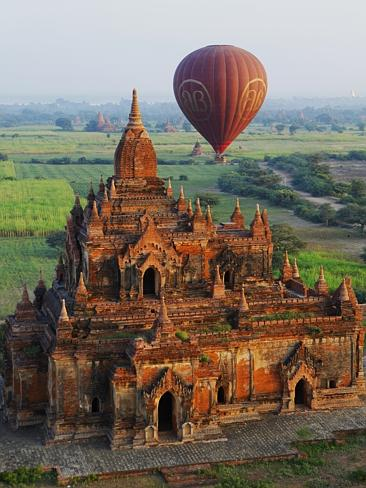 A hot air balloon hovers over a temple at Bagan.