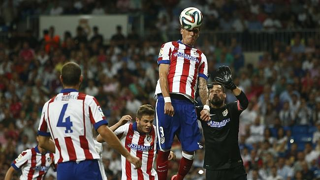 Atletico's Mandzukic top, jumps for the ball in between plyers during a Spanish Supercup