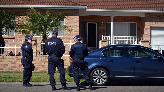 Police officers stand guard outside a house during a raid in Guildford. Picture: AFP PHOT