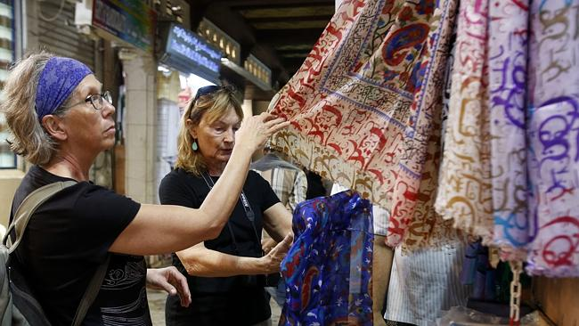 Tourists look at scarves at a Muscat market.