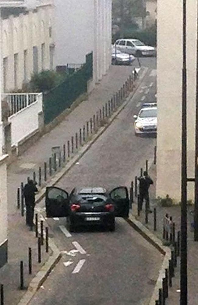 Armed ... Armed gunmen face police officers near the offices of the French satirical news