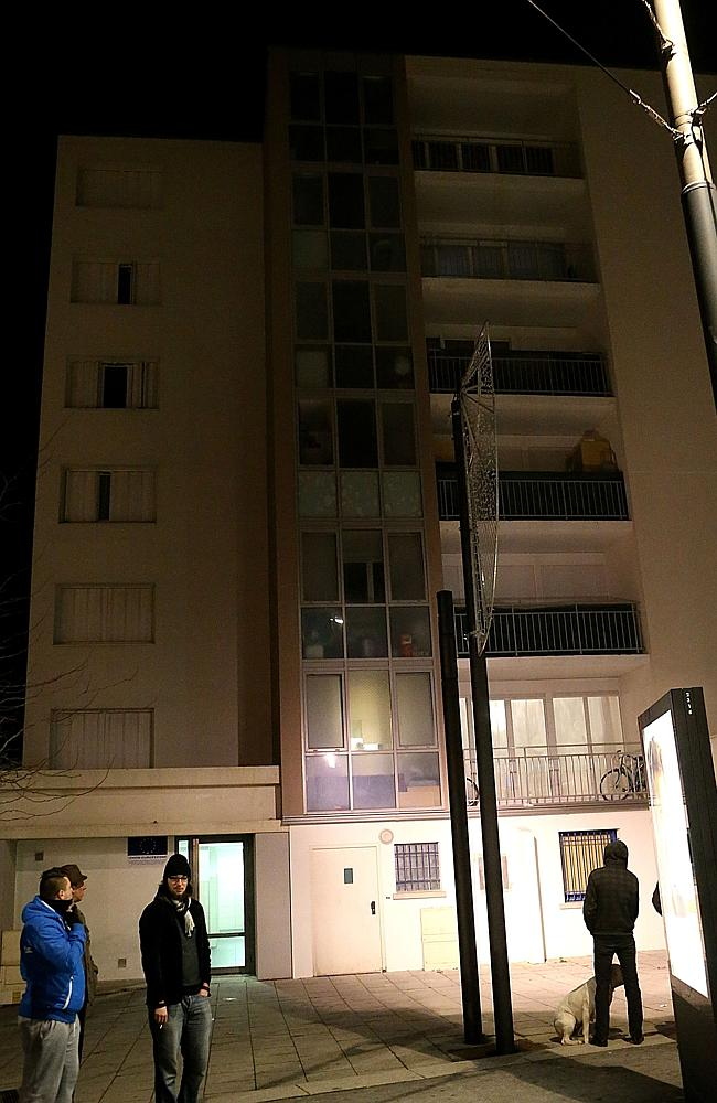 Residents wait outside as French police search the Reims apartment block