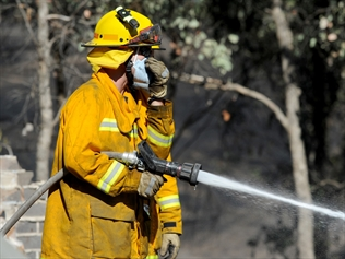A CFA firefighter puts out a fire
