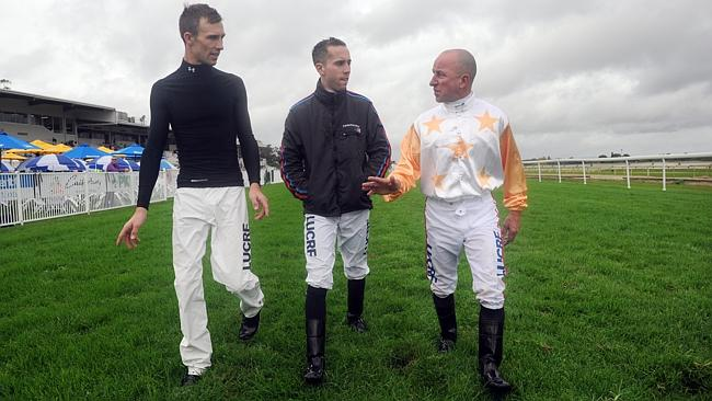 Jockeys Tye England, Brenton Avdulla and Jim Cassidy inspect the track after race one at
