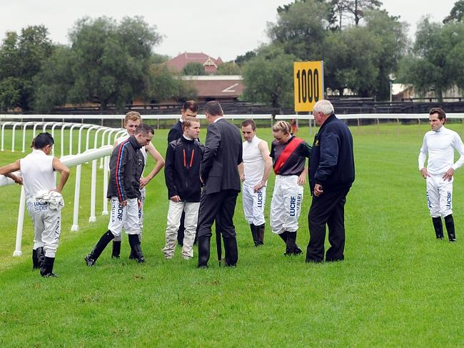 Jockeys and chief steward Ray Murrihy inspect an area of particular concern at the 900m o