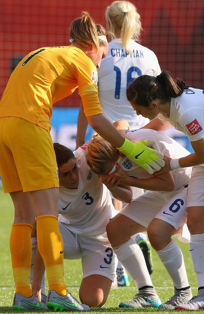Laura Bassett of England is comforted by team mates.