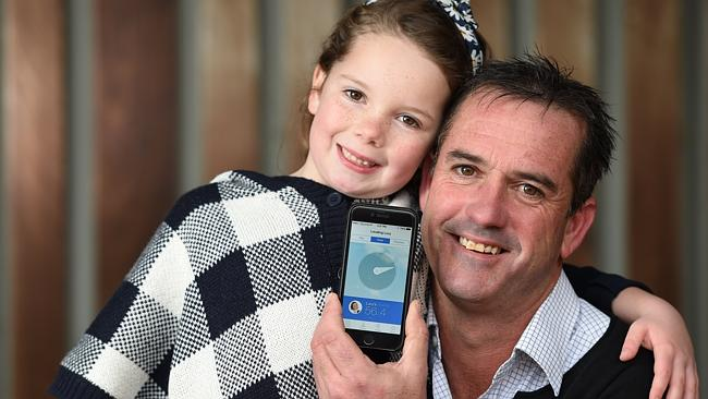 Mornington trainer Jason Petch with daughter Lucy and the Sky Nanny app on his mobile pho