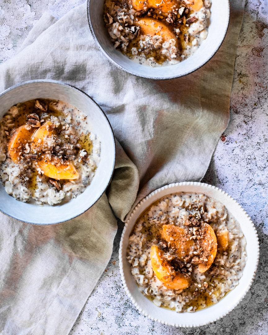 3 coconut oatmeal bowls with peaches and walnuts