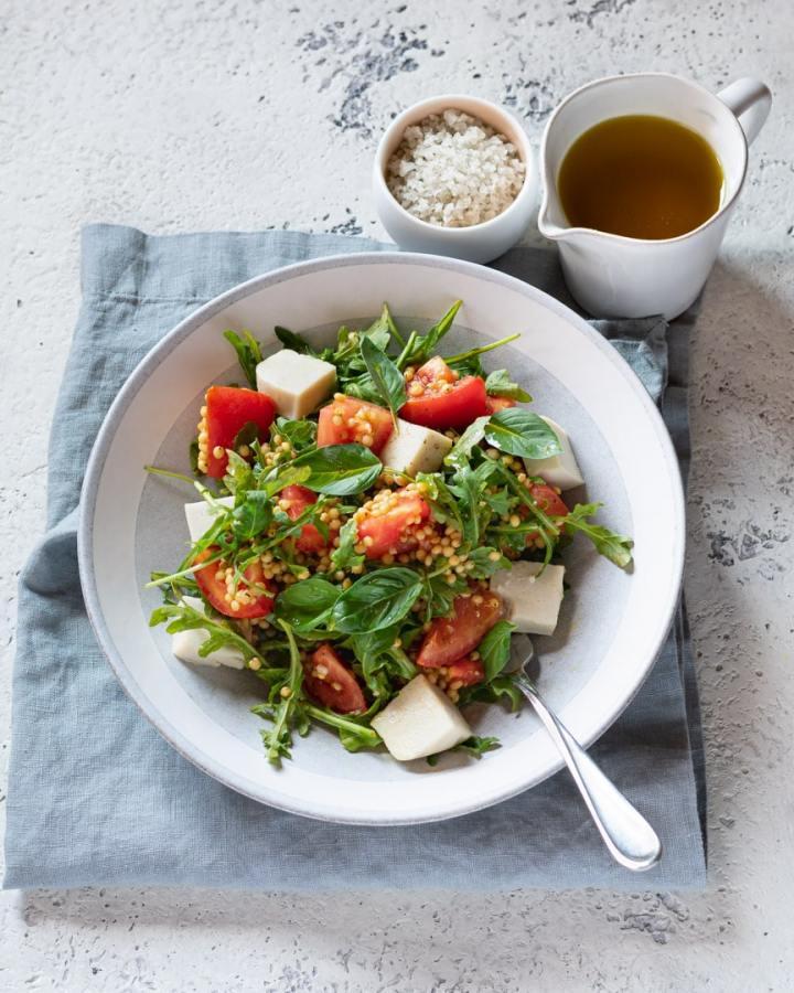 bowl of sorghum caprese salad with garlic balsamic dressing and sea salt