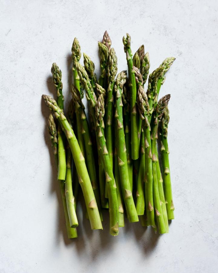raw asparagus stalks on grey background