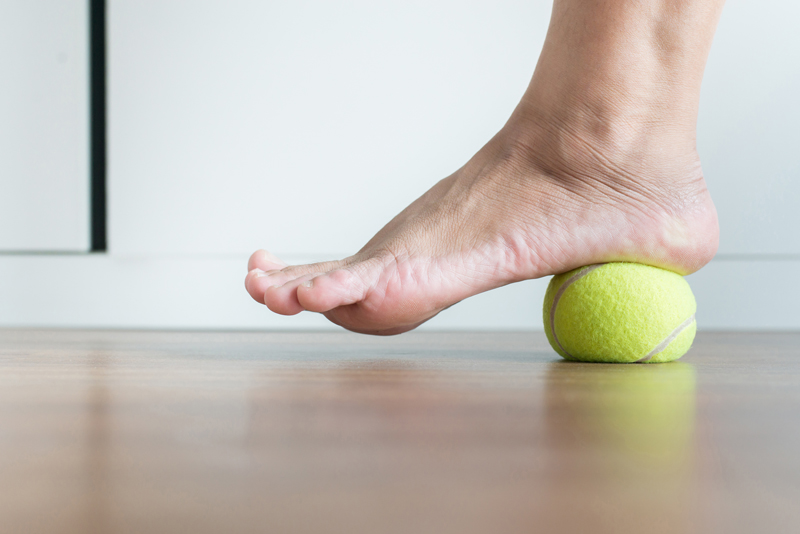 Women massaging foot with tennis ball