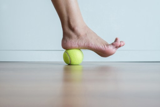 Woman massages her foot with a tennis ball. Feet soles or heel massage for plantar fasciitis.