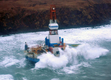 Waves crash over the mobile offshore drilling unit Kulluk where it sits aground on the southeast side of Sitkalidak Island, Alaska, Jan. 1, 2013. (U.S. Coast Guard)