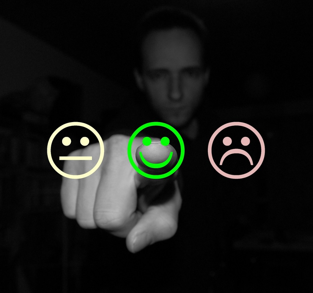 person giving feedback using smiley face buttons