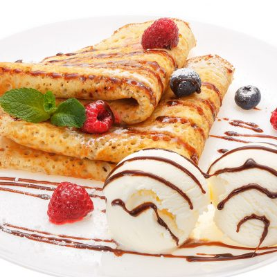 Serving pancakes with ice cream and fresh berries on the plate. Decorated with chocolate syrup.  Isolated on white background.