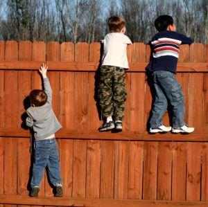 children-climbing-fence