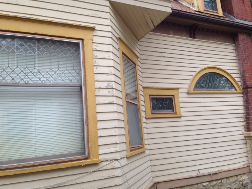 This is the outside of the bedroom bay. Note the beveled leaded glass windows. The small window to the right is under the stair; the arched window is the main stair window.