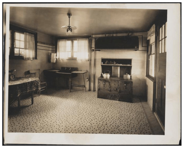 1915? Tile floor and walls. Cast-iron range. Love the light fixture. Sink with wood drain boards. Image courtesy Museum of the City of New York.
