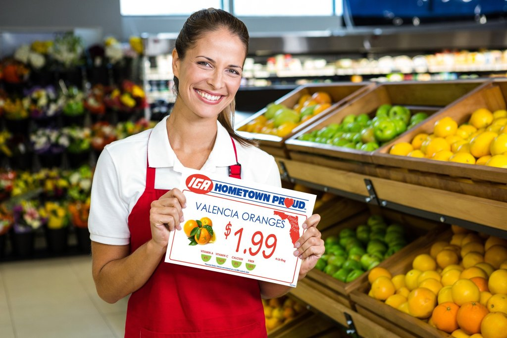 Smiling grocer holding IGA sign created with DESIGN-R-LABELS