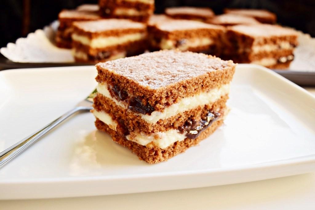 Porție de prăjitură cu cremă de cocos și caramel cu cacao pe o farfurie albă